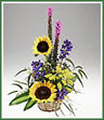 A natural basket of solidaster, liatris, sunflowers, delphinium and foliage.