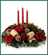 The Celebration of the Season Centerpiece is a grand display of holiday elegance. Red roses and spray roses pop against a backdrop of assorted holiday greens and variegated holly that beautifully encircle three red taper candles. Accented with gold pinecones and gold metallic brocade ribbon this centerpiece creates a warm and enchanting glow to benefit their holiday festivities.