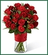 The Spirit of the Season Bouquet bursts with beauty and cheer to dazzle your special recipient with its holiday beauty. Brilliant red spray roses and mini carnations are brought together with burgundy mini carnations, red hypericum berries and assorted holiday greens in a clear glass vase accented with a thick red designer ribbon to create a special sentiment of seasonal wishes and caring kindness