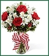 The Holiday Enchantment Bouquet is blooming with bright seasonal cheer to bring Christmas joy to your special recipient. Rich red roses are surrounded by white Peruvian lilies, variegated holly and assorted holiday greens perfectly arranged in a clear glass vase tied at the neck with a candy cane striped ribbon to create a fantastic holiday look.