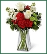 The Christmas Peace Bouquet captures the elegance of the season at every turn. White roses, red carnations, white stock, green button poms, holly and assorted holiday greens are arranged perfectly in a modern clear square glass vase to create a gift that extends warm wishes for a season of peace and togetherness
