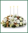 The Season's Glow Centerpiece blooms with winter elegance and holiday enchantment to grace your Christmas celebrations. White LA hybrid lilies, carnations, chrysanthemums and statice are arranged amongst holiday greens and accented with gold pinecones and a gold plaid French wired ribbon for an exquisite look. Arranged to encircle 3 white taper candles, this stunning arrangement will bring a sweet sophistication to your holiday festivities