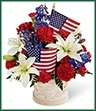 The American Glory Bouquet bursts with patriotic pride and heartfelt beauty. Blue delphinium, bright red carnations and mini carnations and brilliant white Asiatic lilies create a spectacular display arranged amongst American Flags in a round whitewash basket, creating a lovely way to celebrate this coming July 4th holiday.