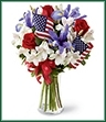The Unity Bouquet sparks the hearts of all Americans with its patriotic beauty and dazzling color. Bright red roses mingle with blue iris arranged amongst white Peruvian lilies and assorted greens. Accented with two American Flags and a red, white and blue ribbon, this stunning bouquet arrives arranged in a clear glass vase to create a gorgeous way to celebrate our Independence Day.