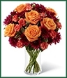 The Autumn Treasures Bouquet is a floral fantasy of fall color displayed in eye-catching jewel tones. Brilliant orange roses and orange mini carnations are accented with burgundy chrysanthemums and lush greens arranged to perfection in a classic clear glass vase to create a warm and dazzling way to send your best wishes for a beautiful harvest season.