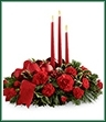 The Lights of the Season Centerpiece is an exquisite way to bring the magic of the holiday season to your celebrations with family and friends. Brilliant red carnations and mini carnations are gorgeously arranged amongst variegated holly and an assortment of holiday greens. Accented with red glass balls and a bright red wired ribbon, this arrangement encircles 3 red taper candles to bring the perfect glow to your festivities