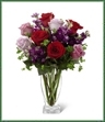The Garden Walk Bouquet is an exquisite expression of natural beauty and grace. Assorted lavender roses, rich red roses, purple stock and lush greens have a fresh look of floral elegance presented in a modern clear glass vase to create a sweet sentiment ideal to celebrate any of life's special moments.